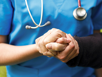 healthcare provider holding hand of an older adult