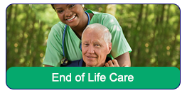 End of Life Care: A health care professional standing behind an elderly man in a wheelchair. She is leaning over and giving the man a hug.